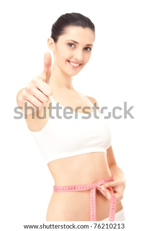 isolated shot,  healthy woman measuring her waistline and giving a thumbs up (focus on the thumb) - stock photo