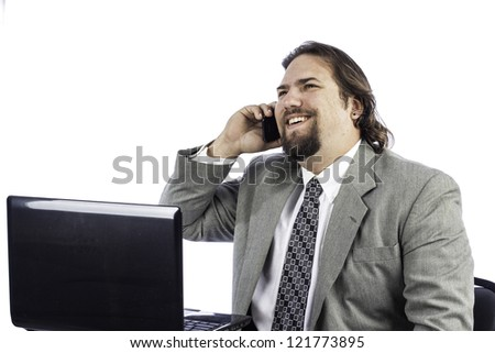 isolated shot of a business man at a laptop talking on a cell phone - stock photo