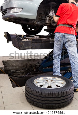 Isolated shot of a mechanic servicing the brake system, with tire on the floor. - stock photo