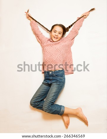 Isolated shot of cute happy girl with long braids jumping up high - stock photo