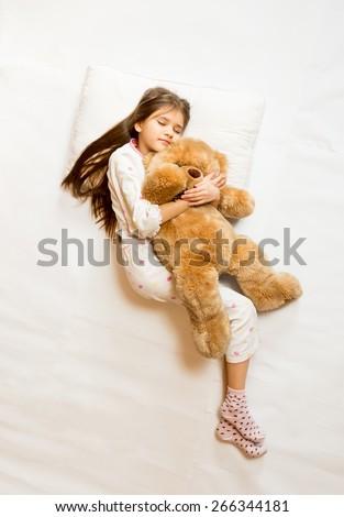 Isolated shot of cute sleeping girl hugging teddy bear - stock photo