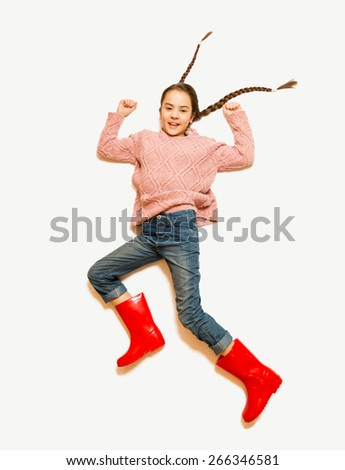 Isolated shot of cute smiling girl in red rubber boots jumping high - stock photo