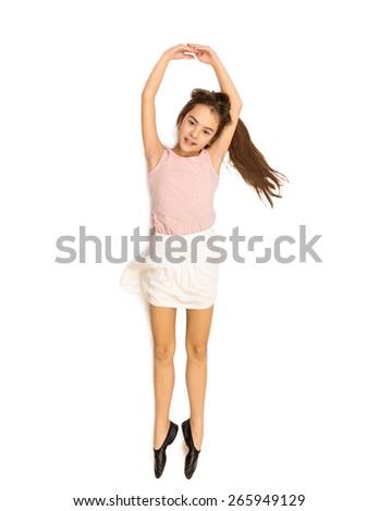 Isolated shot of happy smiling girl lying on floor and dancing ballet - stock photo