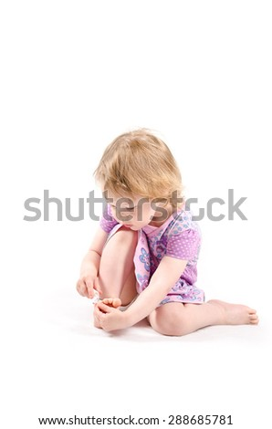 Isolated shot of little fashionista playing with a nail oil - stock photo
