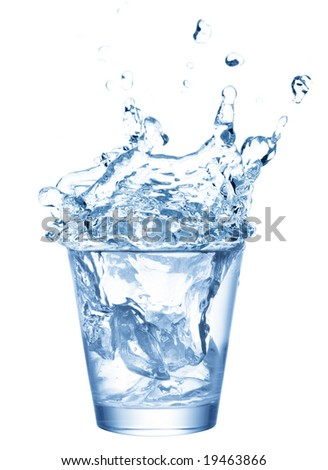 Isolated shot of water splashing from ice cubes being dropped in a glass. - stock photo