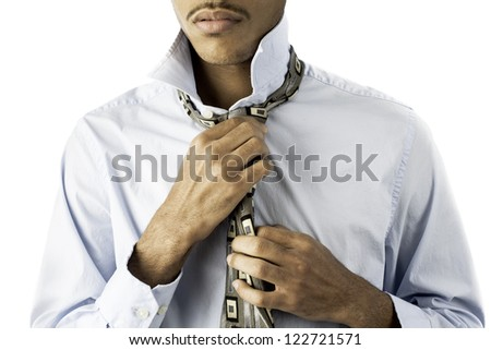 isolated shot showing a young african american black male finishing tying a tie. - stock photo