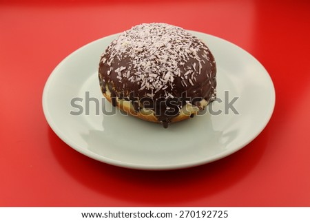 Isolated single chocolate donut with sprinkled coconut pieces on a plate - stock photo