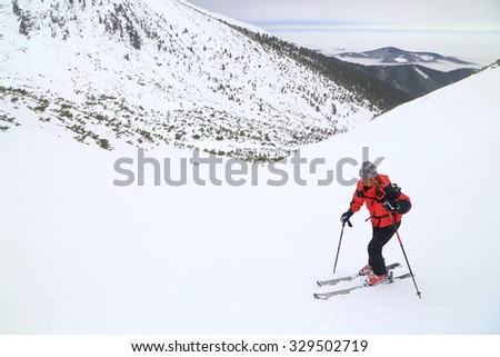 Isolated ski mountaineer climbs moderate slope on snow covered mountain  - stock photo