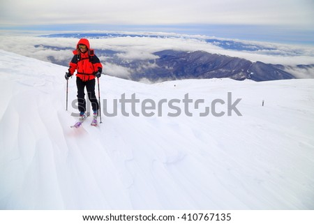 Isolated ski mountaineer traversing a snow covered mountain in cloudy day - stock photo