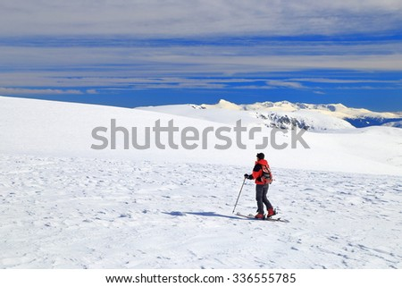 Isolated ski mountaineer traversing a vast plateau covered with snow in winter - stock photo
