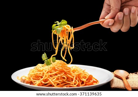 Isolated Spaghetti on black background with clipping path, someone is being rolled spaghetti      on white plate by wooden fork