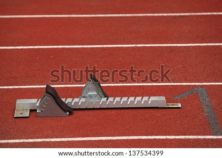 isolated starting block on an athletics track - stock photo