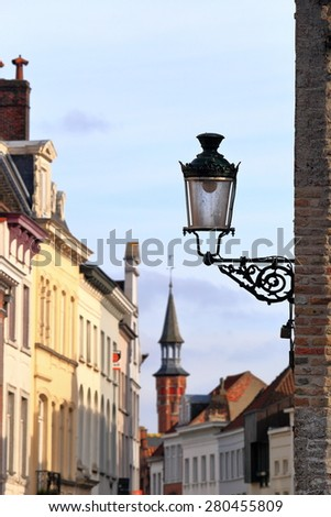 Isolated street lamp on a wall inside Bruges old town, Belgium - stock photo