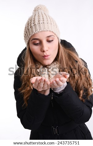 isolated studio portrait of happy young woman in winter outfit blowing a kiss in her hands