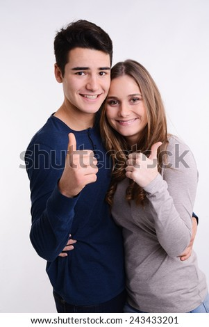 isolated studio portrait of successful young couple showing thumbs up standing on white background - stock photo