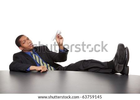 Isolated studio shot of a bored businessman with his feet on the desk ready to launch a paper airplane. - stock photo