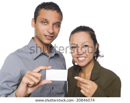 Isolated studio shot of a businessman and businesswoman displaying a business card and pointing at it. - stock photo