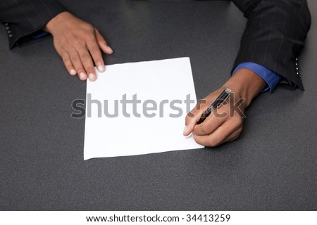 Isolated studio shot of a businessman's hands pointing to the end of a blank page ready for your copy. - stock photo