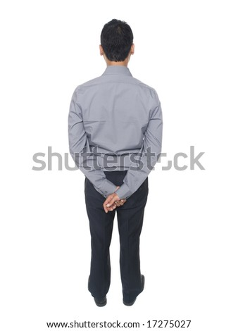 Isolated studio shot of a businessman standing patiently. - stock photo