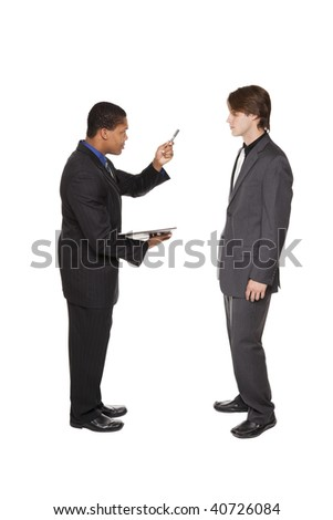 Isolated studio shot of a businessmen shaking his pen at another businessman in warning during a review.
