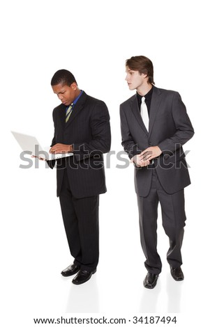 Isolated studio shot of a businessmen snooping over another businessman's shoulder as he enters his password on his laptop. - stock photo