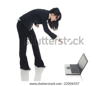 Isolated studio shot of a businesswoman leaning over and pointing angrily at a laptop. - stock photo