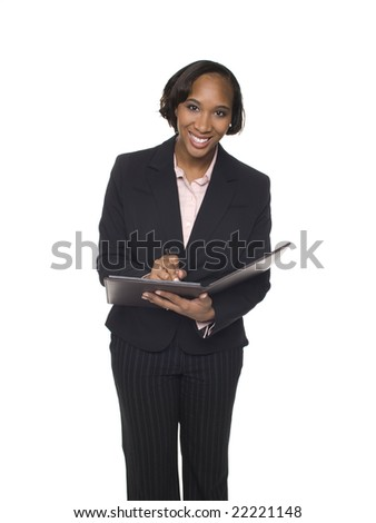 Isolated studio shot of a businesswoman smiling at the camera while taking notes in her notebook.