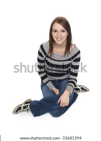 Isolated studio shot of a casually dressed young adult woman sitting on the floor and smiling up at the camera. - stock photo