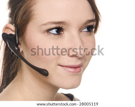 Isolated studio shot of a casually dressed young adult woman wearing a telephone headset and looking away from the camera. - stock photo