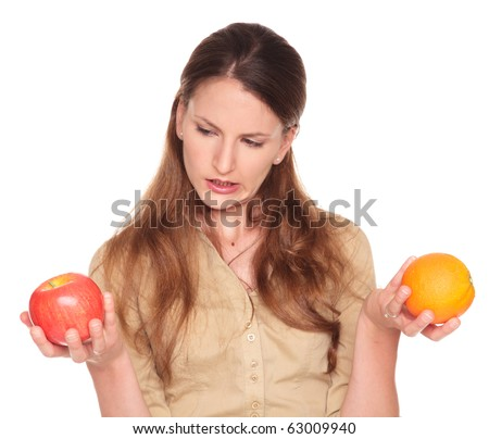 Isolated studio shot of a Caucasian businesswoman comparing an apple to an orange and trying to make a decision. - stock photo