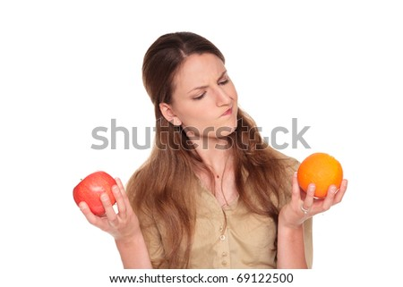 Isolated studio shot of a Caucasian businesswoman making a difficult choice between an apple and orange - stock photo