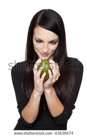 Isolated studio shot of a dark haired caucasian woman looking happily at a vibrant fresh lime.