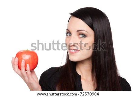 Isolated studio shot of a dark haired caucasian woman looking happily at vibrant fresh fruit.