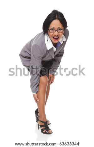 Isolated studio shot of a Latina businesswoman bending over and clutching her leg while looking at the camera. - stock photo