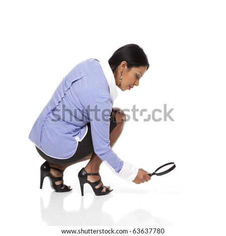 Isolated studio shot of a Latina businesswoman crouching as she uses a magnifying glass to examine a trail on the ground. - stock photo
