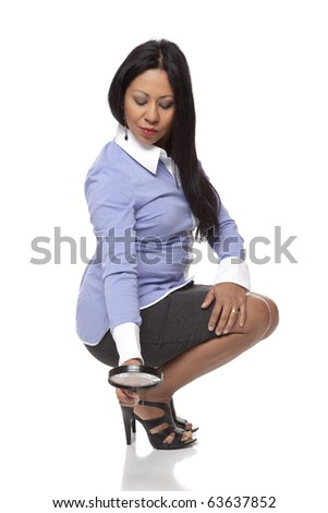 Isolated studio shot of a Latina businesswoman searching for something using a magnifying glass. - stock photo
