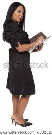 Isolated studio shot of a Latina businesswoman taking notes on a notepad while standing. - stock photo