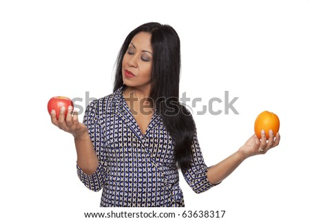 Isolated studio shot of a Latina woman comparing an apple to an orange, deciding what to eat for her healthy diet. - stock photo
