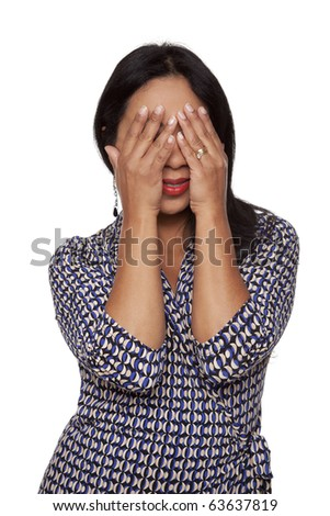 Isolated studio shot of a Latina woman covering her face with her hands and peeking out through her fingers. - stock photo