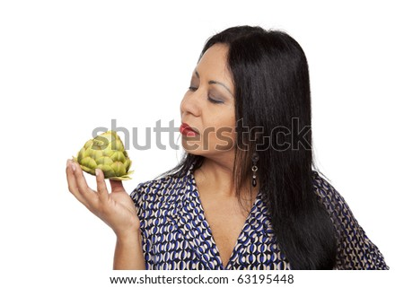Isolated studio shot of a Latina woman examining an artichoke, deciding what to eat for her healthy diet. - stock photo