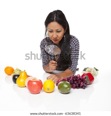 Isolated studio shot of a Latina woman examining fruits and vegetables, deciding what to eat for her healthy diet. - stock photo