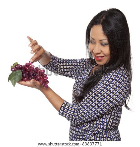 Isolated studio shot of a Latina woman examining grapes, deciding what to eat for her healthy diet. - stock photo