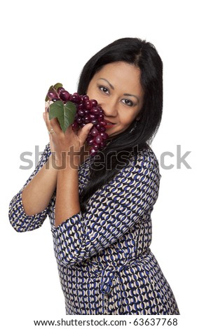 Isolated studio shot of a Latina woman smelling grapes, deciding what to eat for her healthy diet. - stock photo