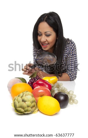 Isolated studio shot of a Latina woman using a magnifying glass to exam fruits and vegetables, deciding what to eat for her healthy diet. - stock photo