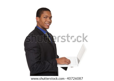Isolated studio shot of a smiling confident businessman looking at the camera while holding a laptop computer. - stock photo