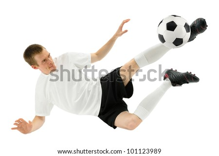 Isolated studio shot of a soccer player kicking the ball in mid-air - stock photo