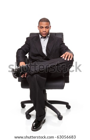 Isolated studio shot of an African American businessman relaxing in a nice office chair. - stock photo