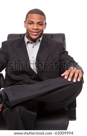 Isolated studio shot of an African American businessman rexlaxing in a nice office chair. - stock photo