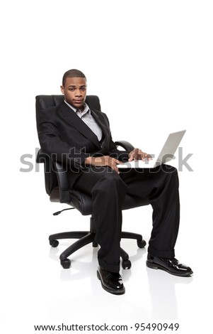 Isolated studio shot of an African American businessman sitting in a nice office chair while working on a laptop computer. - stock photo