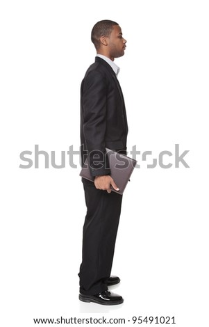 Isolated studio shot of an African American businessman standing and carrying a notepad. - stock photo